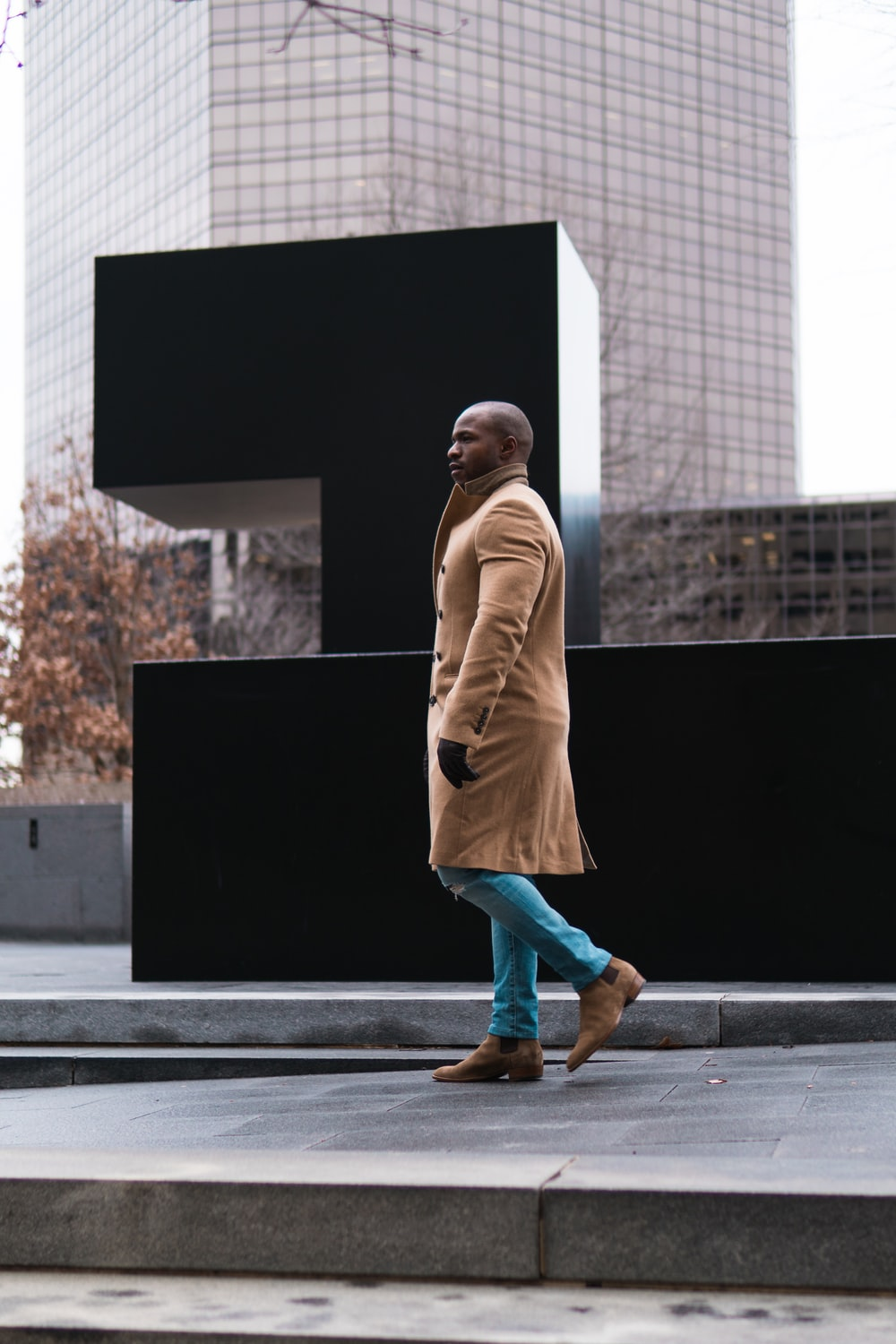 man wearing brown coat walking near black monument during daytime