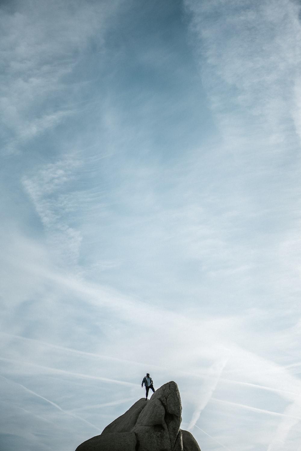 man standing on cliff under white sky