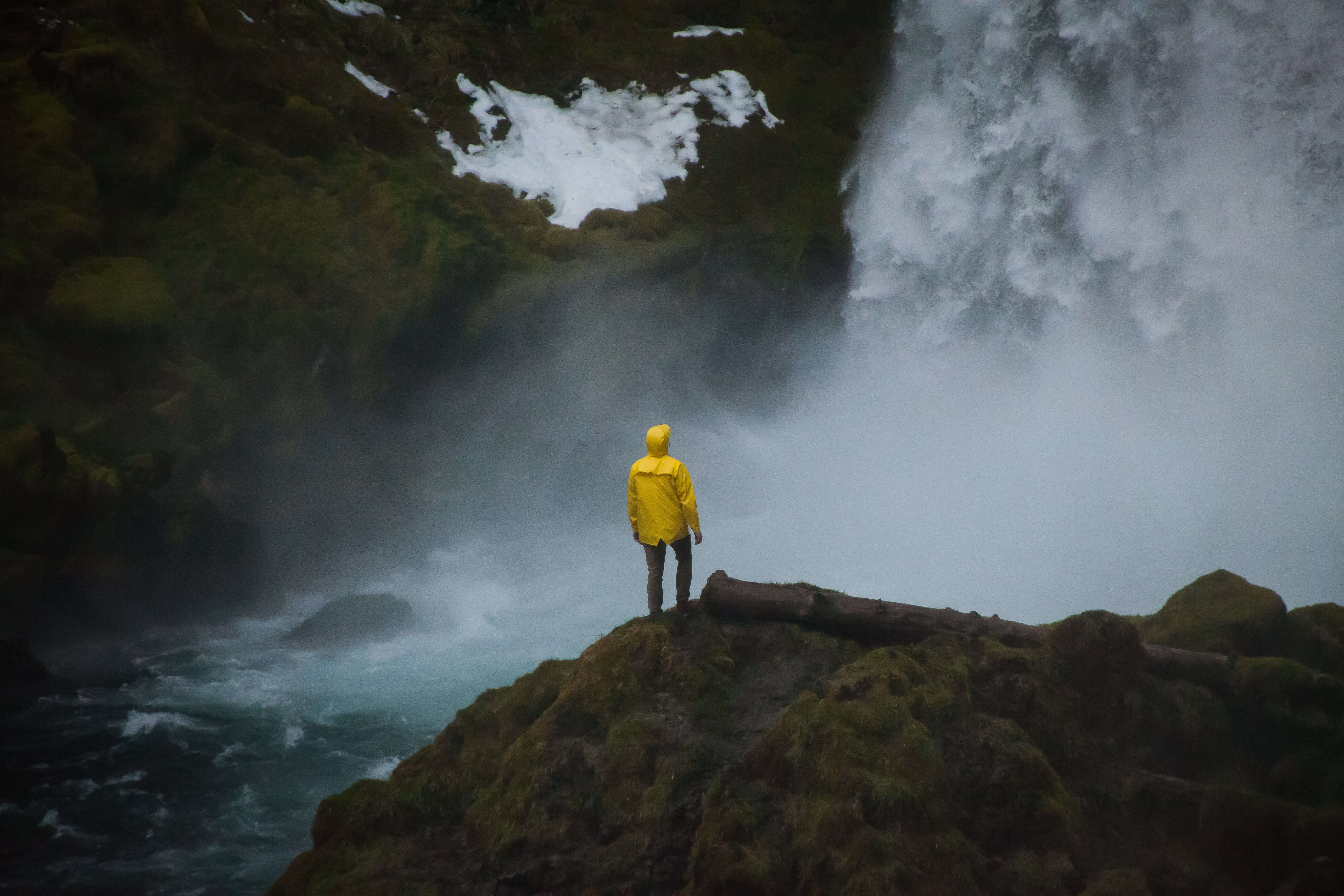 person in yellow coat standing near waterfalls during daytime