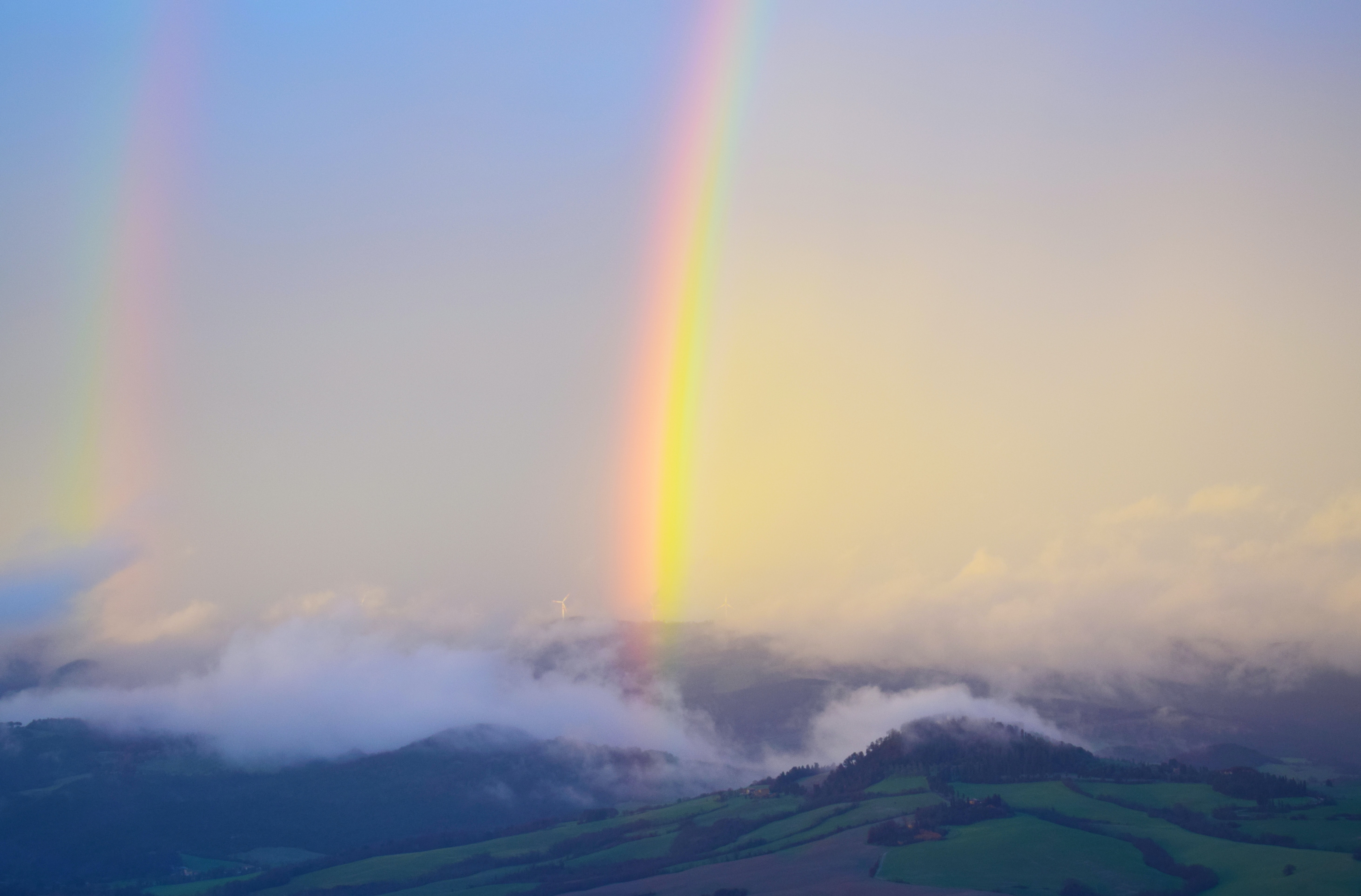 rainbow on brown mountain covered with fogs