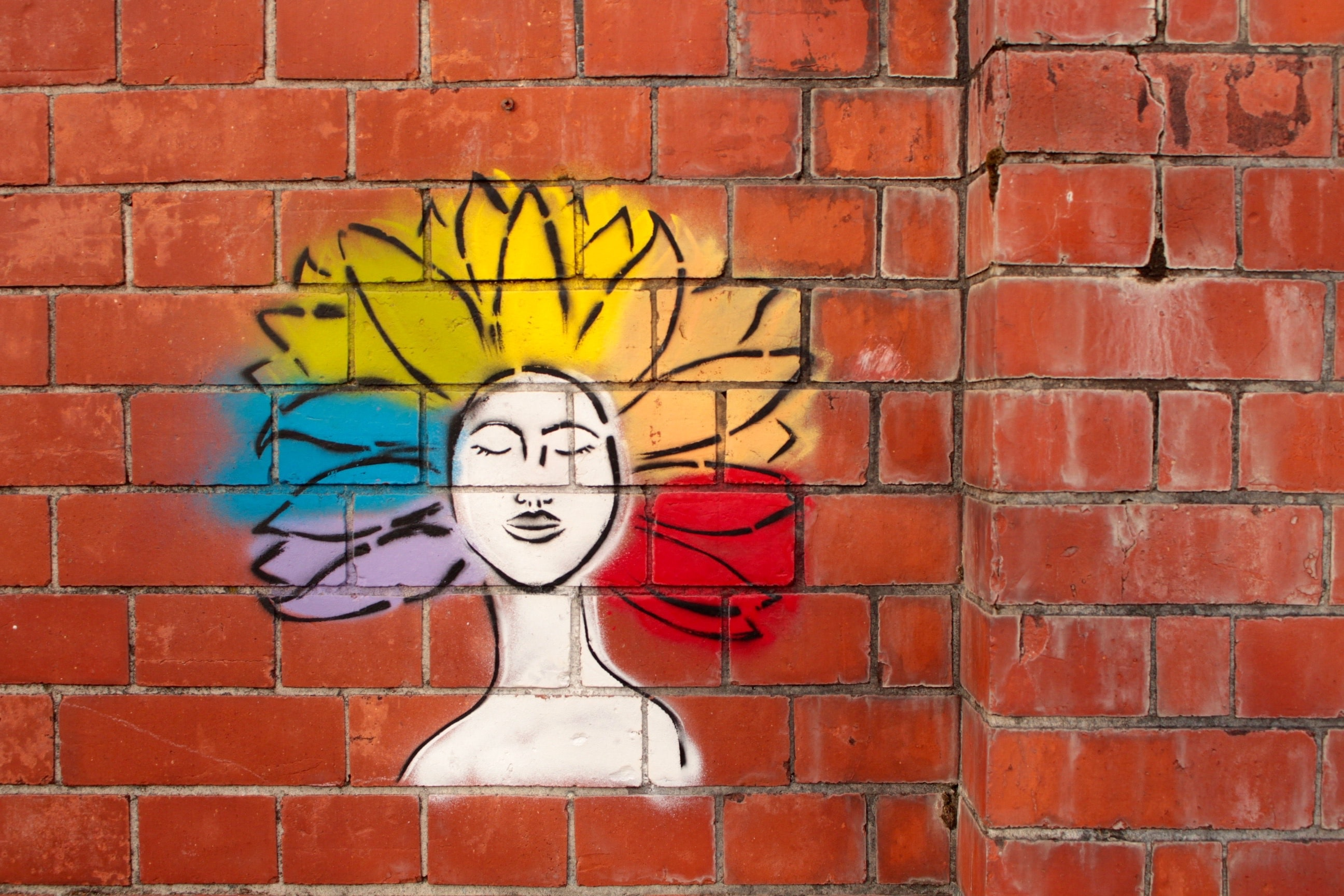 paint spray art of woman on brown brick wall