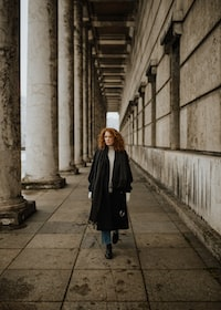 woman in black coat walking on brown tile flooring