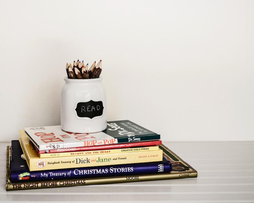 white ceramic pencil organizer on top of stack of books