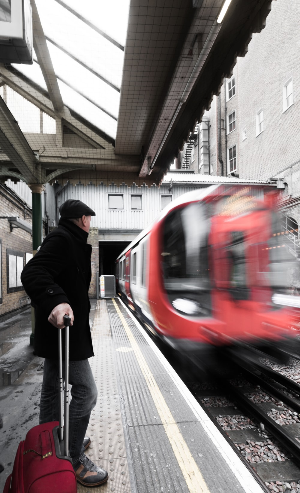 man holding luggage waiting on railway with red train passing by