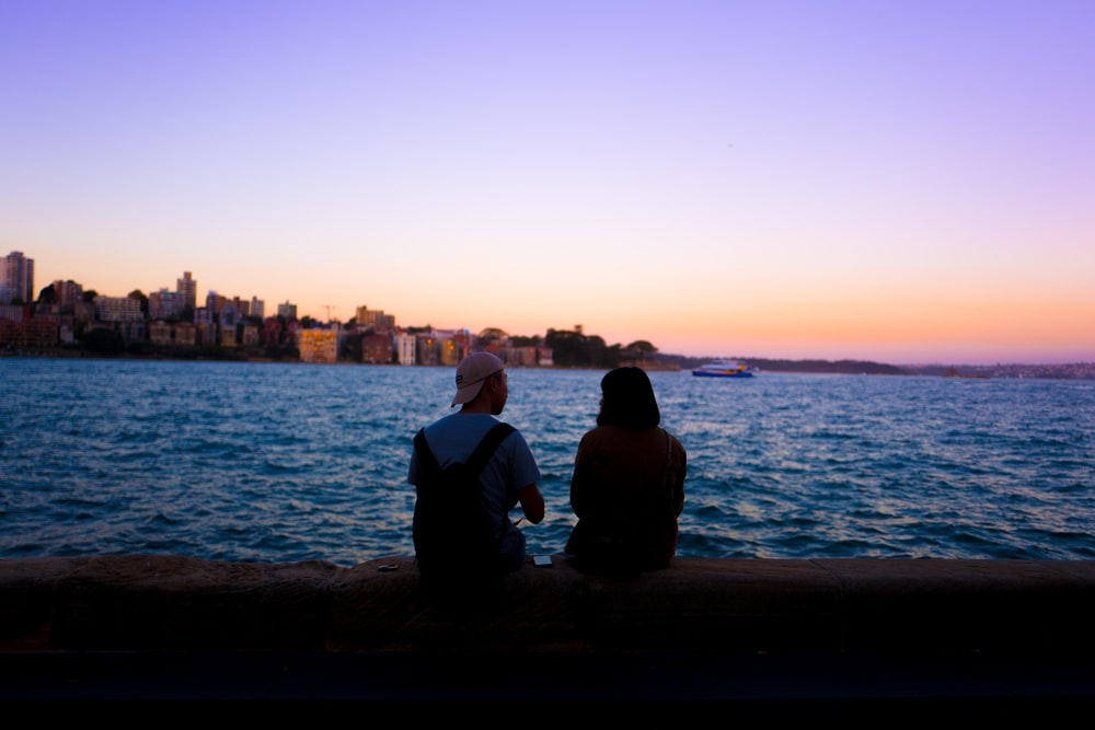 man and woman sitting facing body of water