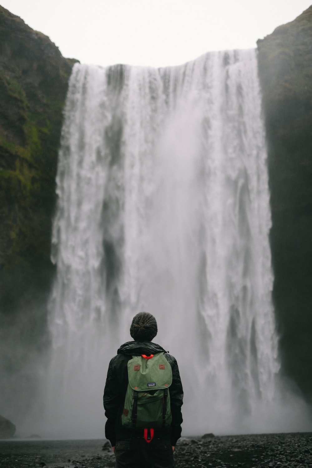 person standing in-front of waterfalls
