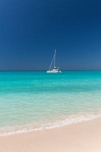 white sailing boat on body of water near coastline