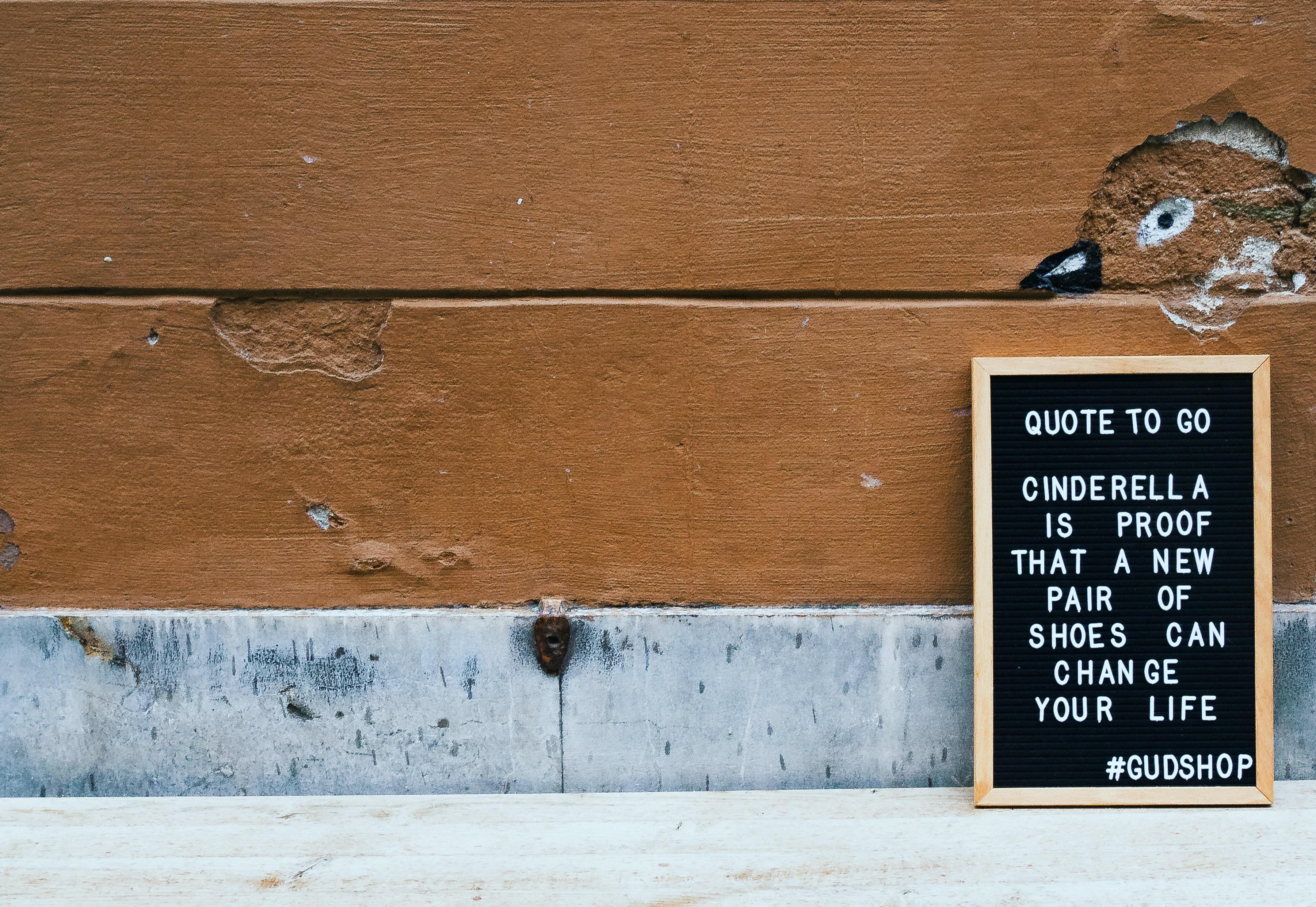 chalkboard leaning on brown concrete wall