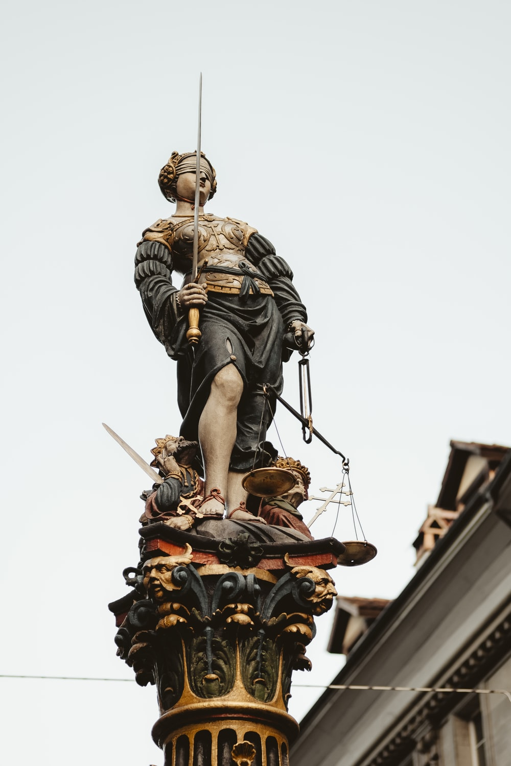 woman holding sword and balance scale statue under white sky