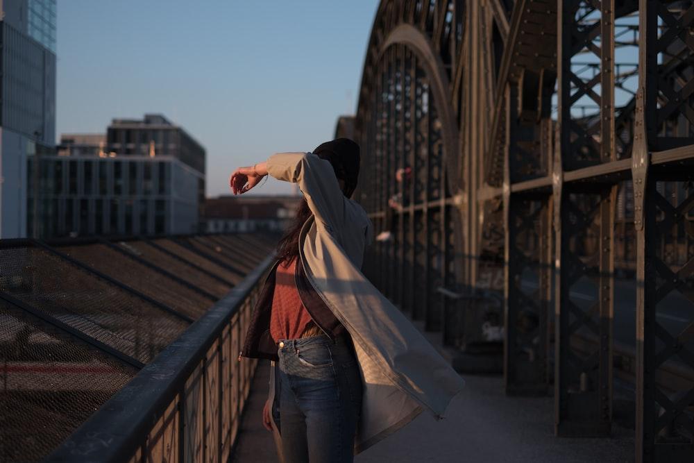 woman standing beside brown steel handrail