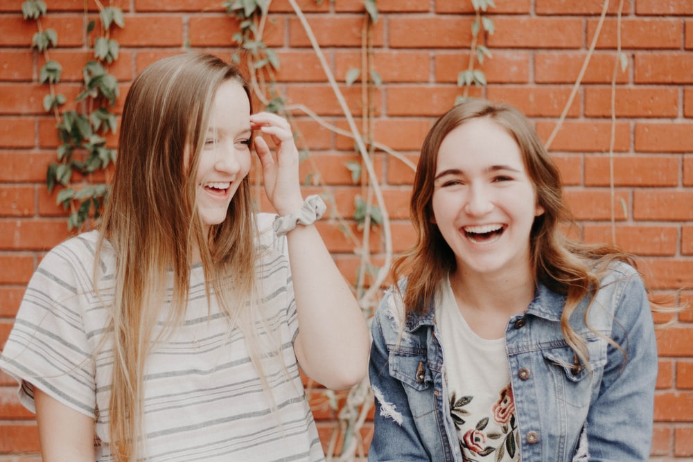 two women smiling while standing near wall