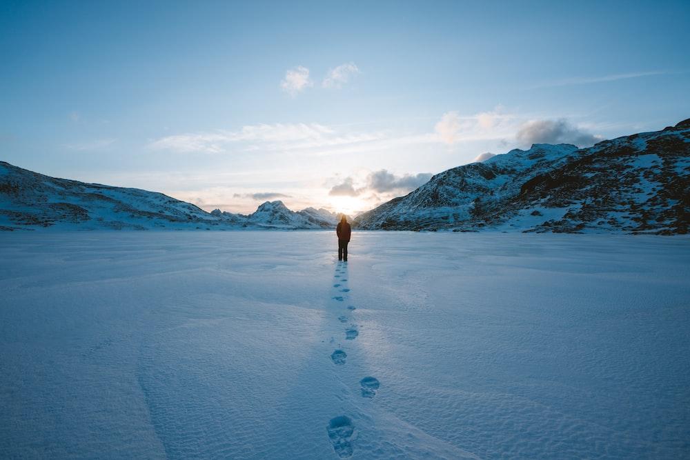 person walking on snow field leaving foot prints