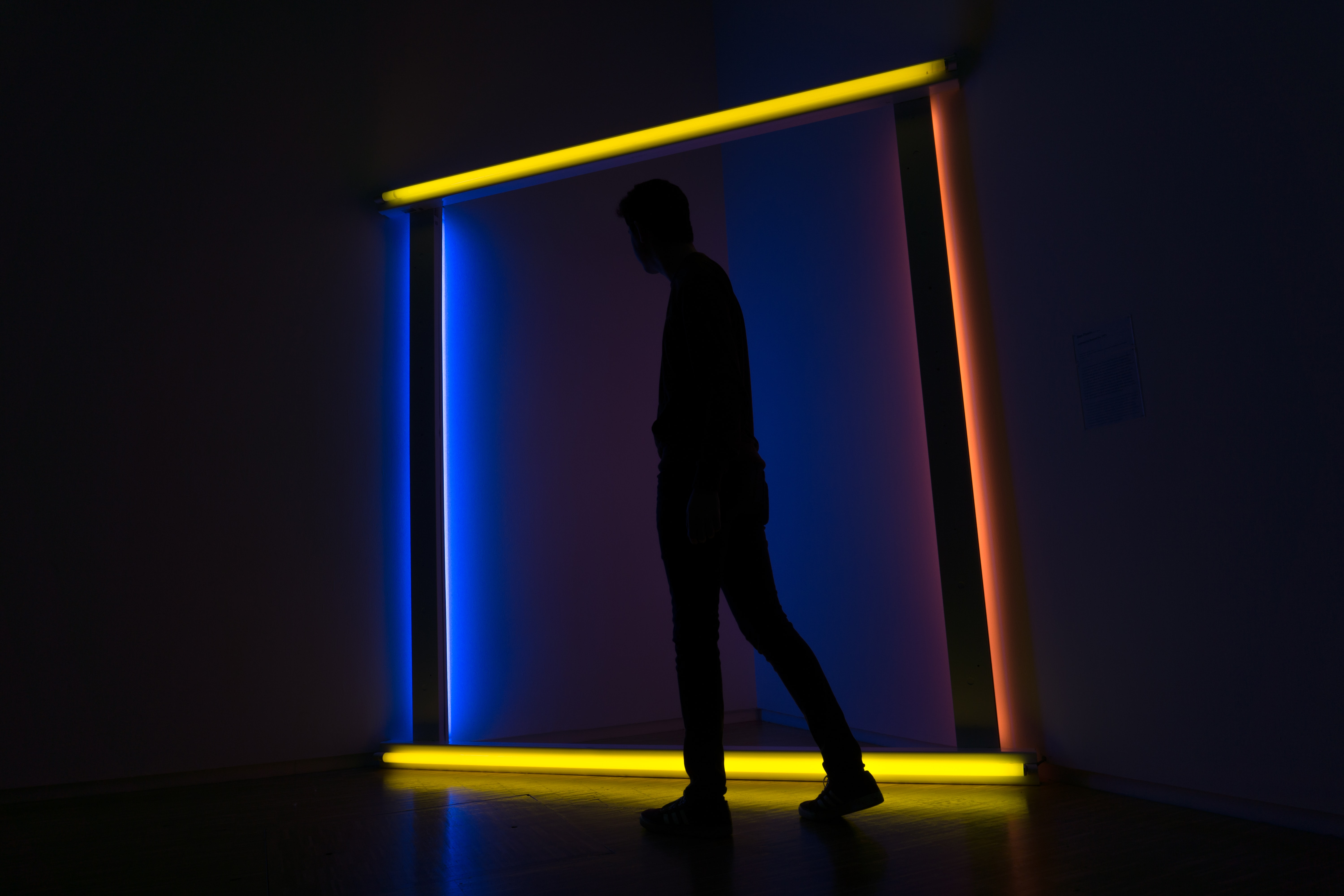 silhouette on man standing on lighted wall