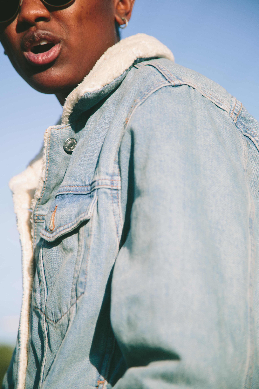 person wearing blue denim sheepskin jacket