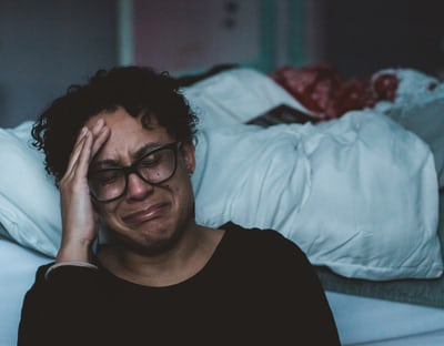 person crying beside bed