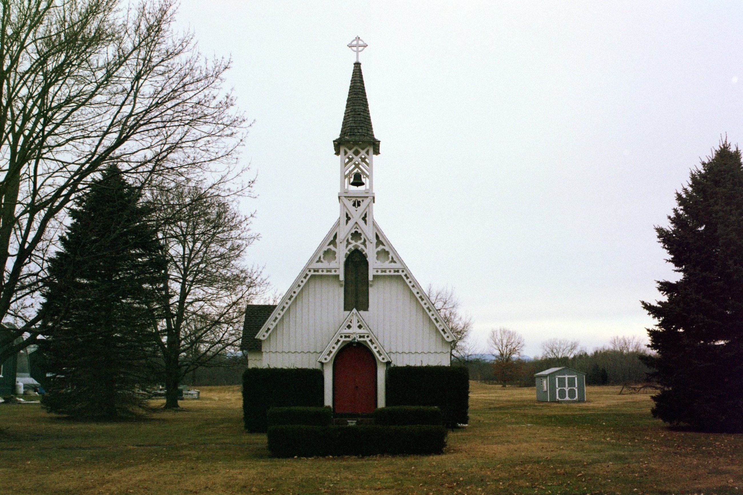 white and red church between trees
