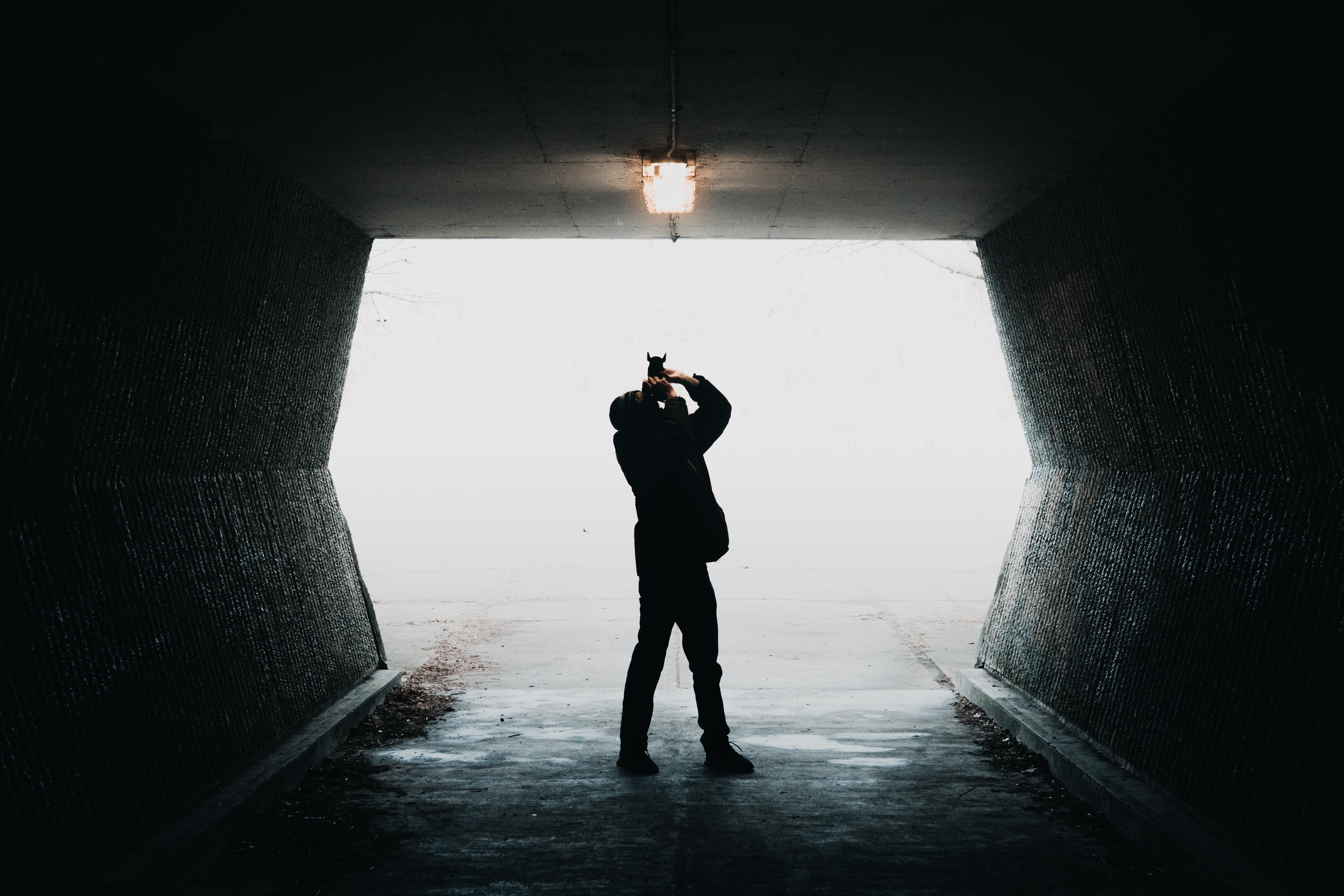 silhouette of man taking photo of light inside tunnel way