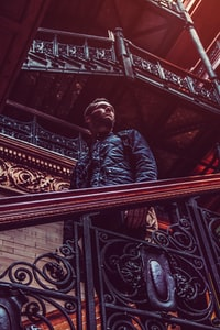 man standing on brown stairs