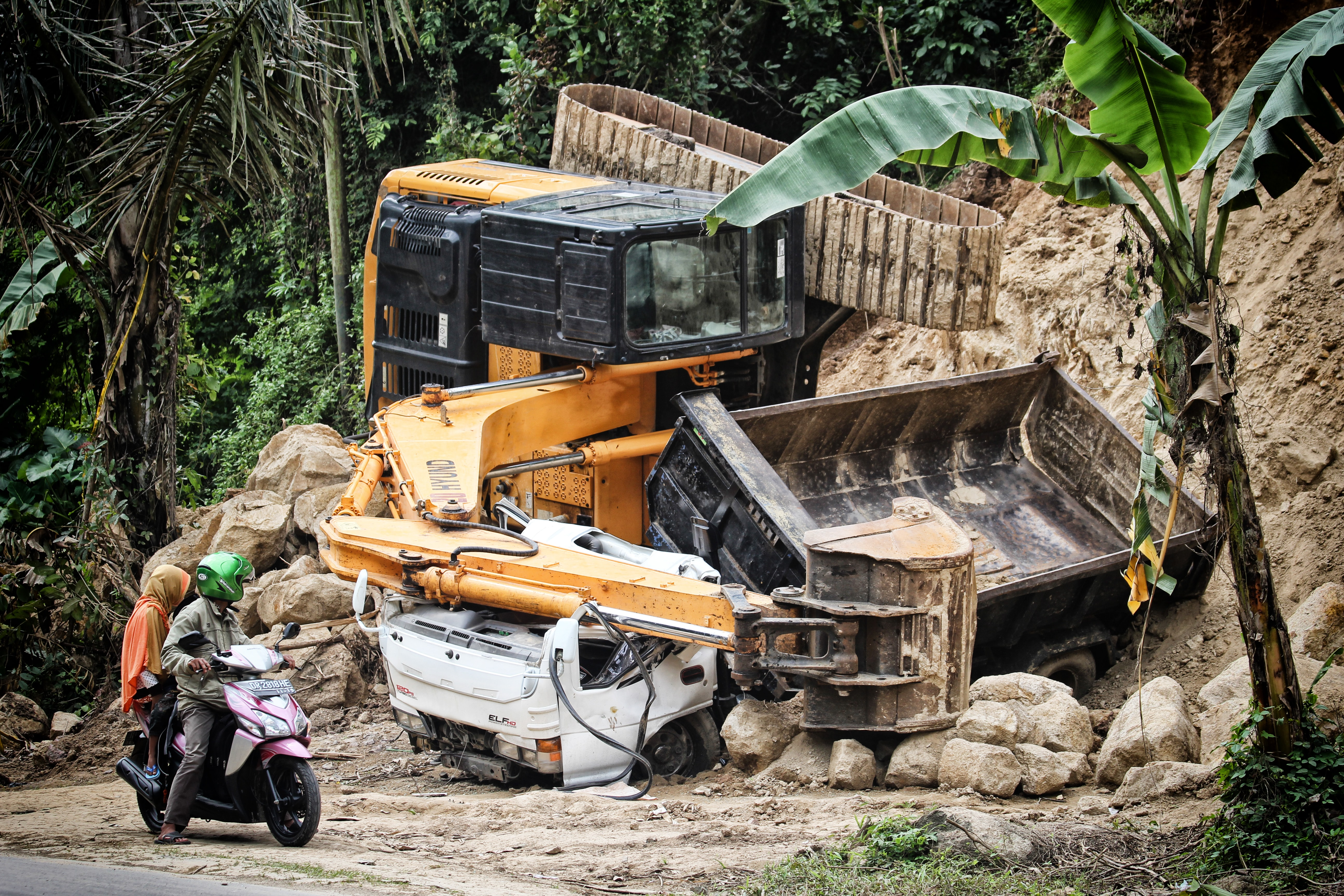 two people riding motorcycle looking at the excavator accident