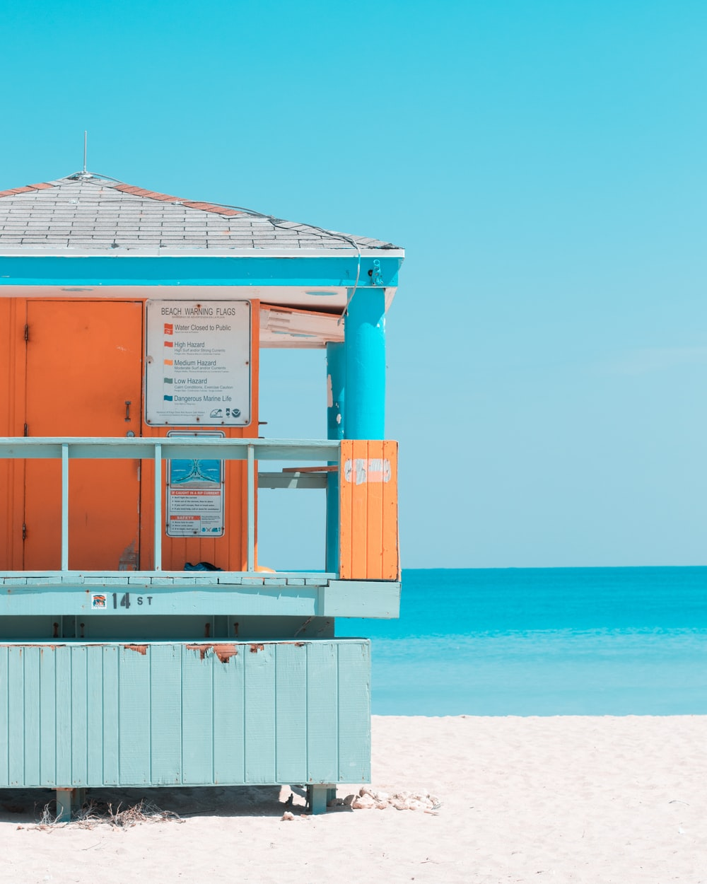 teal, gray, and orange house near seashore during daytime