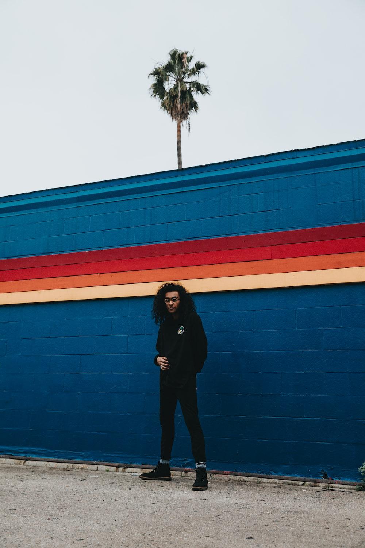man standing beside blue concrete wall