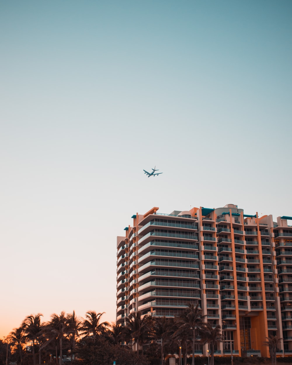 gray airplane above concrete high-rise building