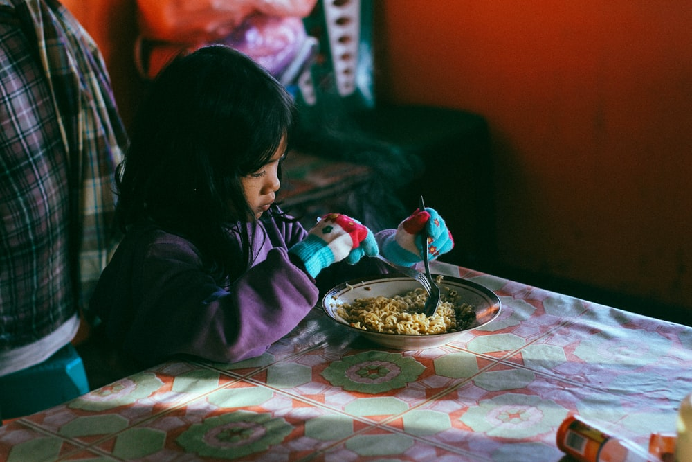girl holding spoon while eating noodles
