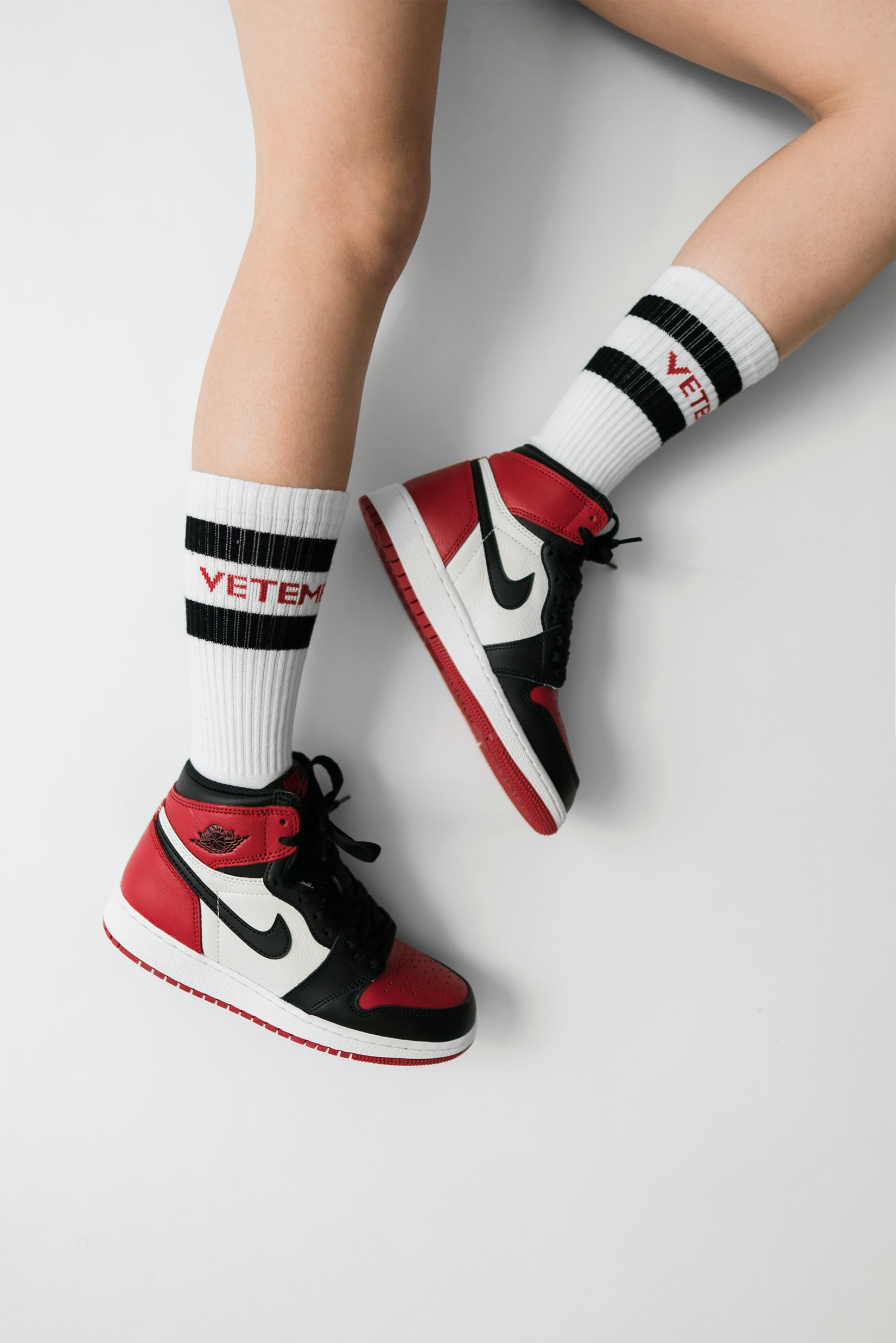 person wearing pair of black toe Air Jordan 1's
