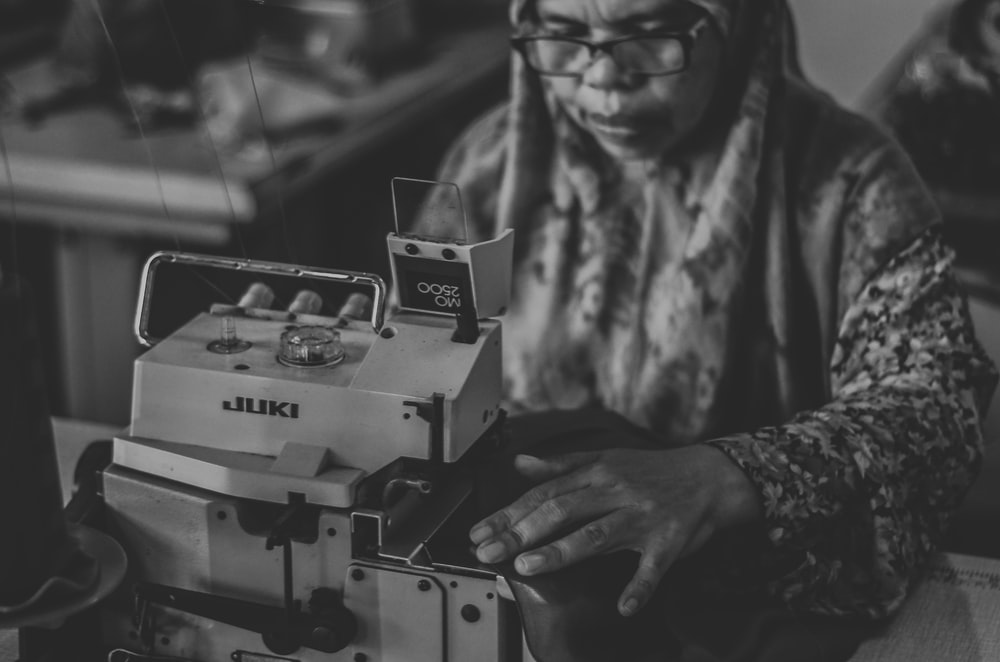 grayscale photography of woman tailoring