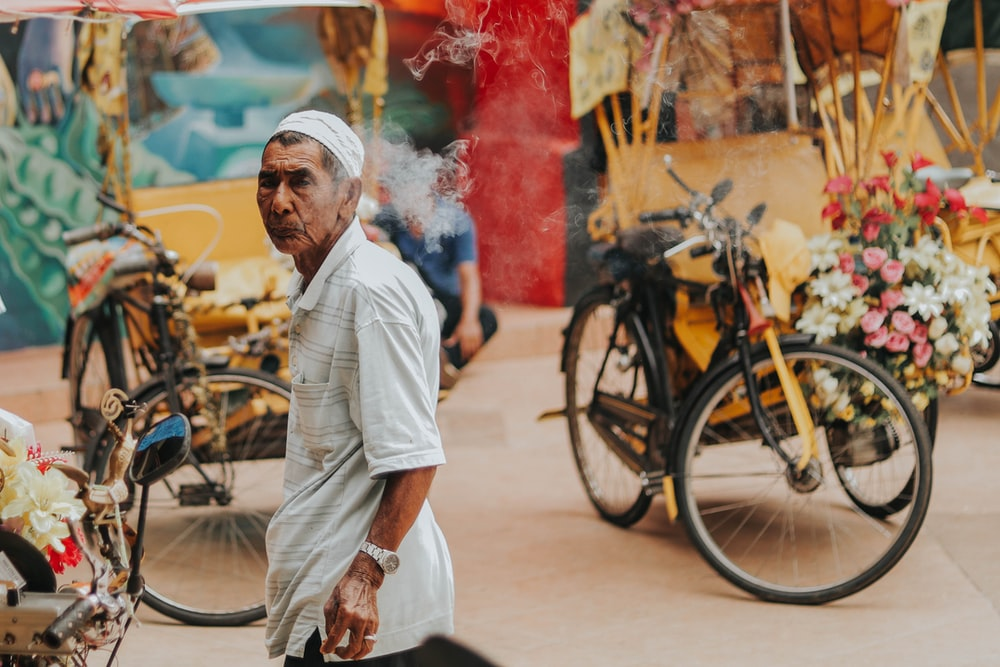 man standing near black bicycle