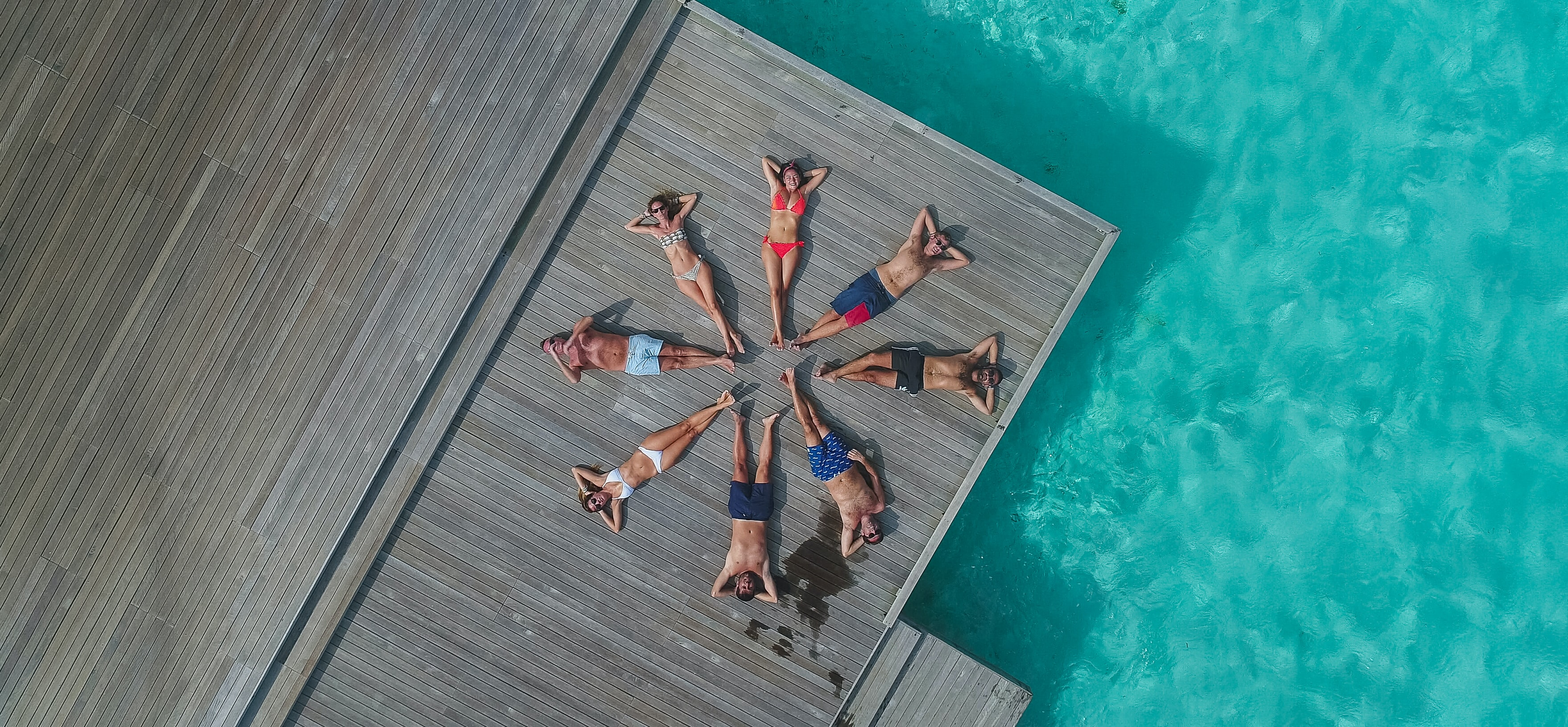 aerial photography of people lying on dock forming circle