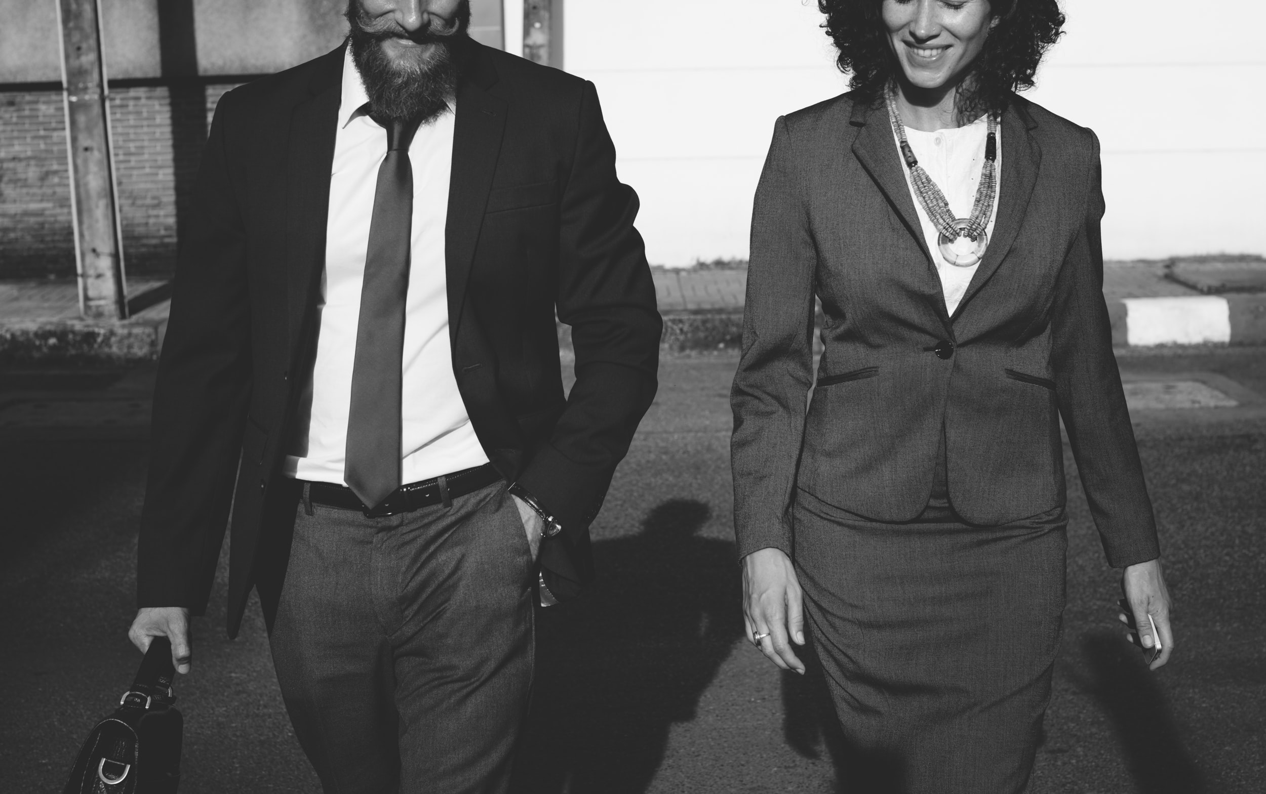 grayscale photography of man standing beside woman while holding handbag