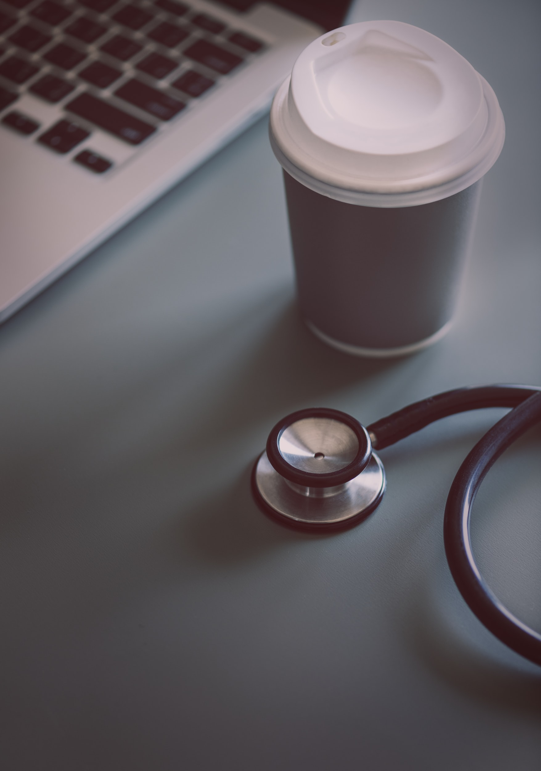 stethoscope beside coffee cup