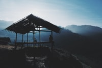 silhouette photo of person sitting on nippa hut on hill in front of mountains surrounded by fogs