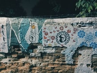 brown brick wall with mural close up photography