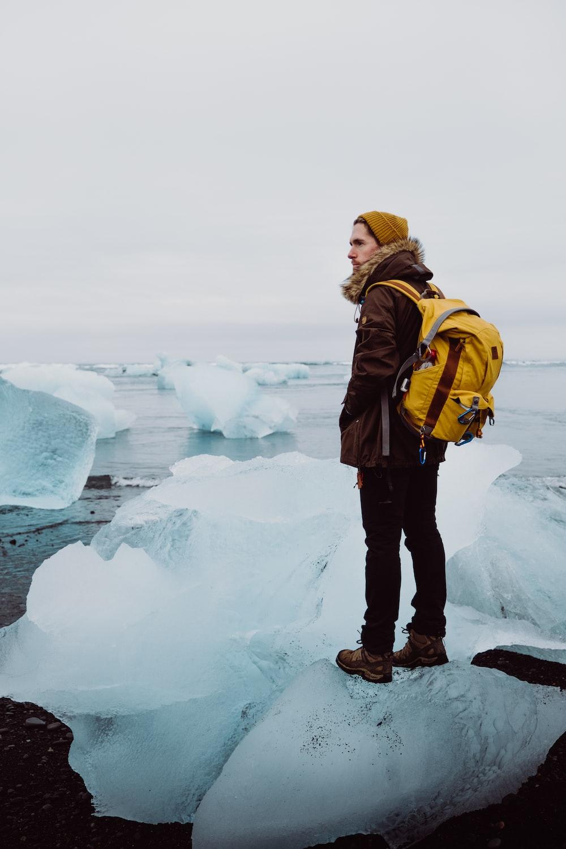 man standing on ice rack under gray sky