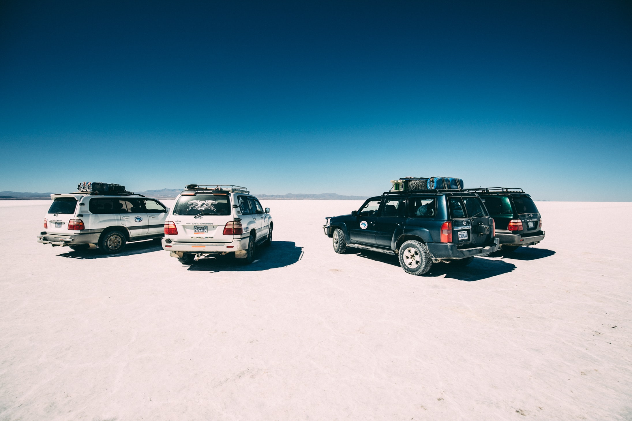 four vehicles on desert at daytime