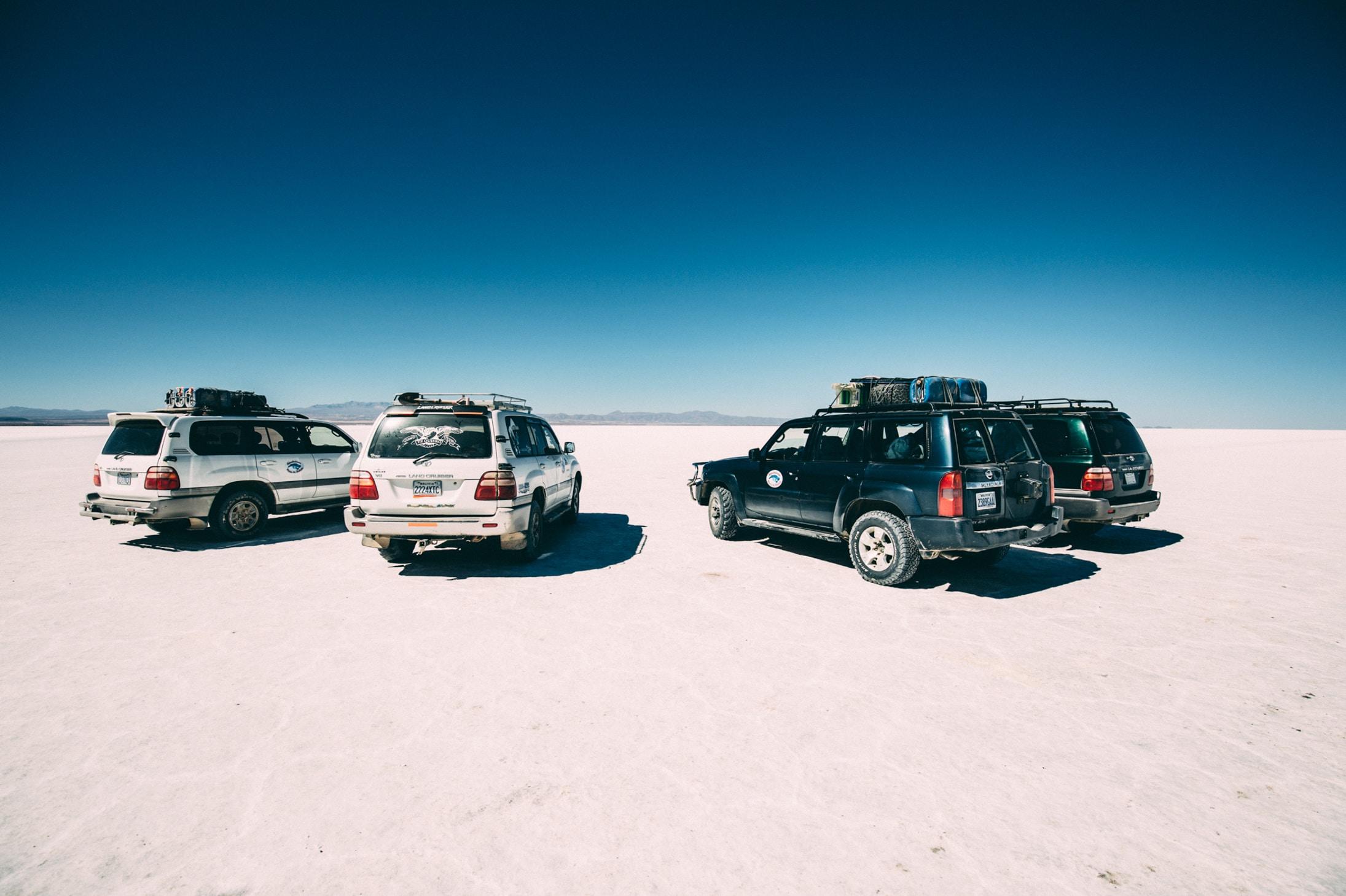 four vehicles on desert at daytime