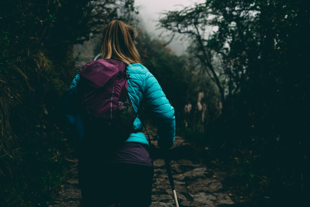 woman wearing bubble jacket walking on pathway between forest