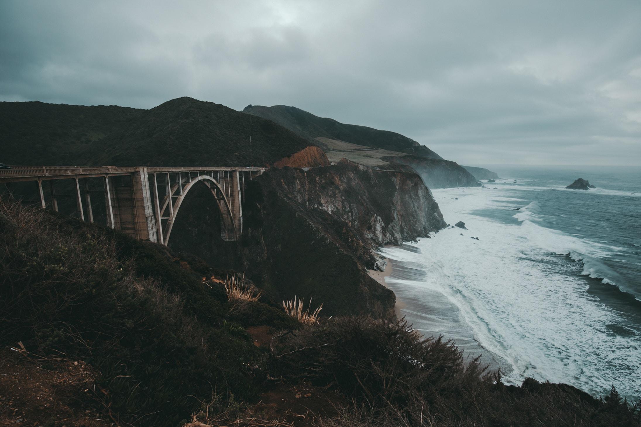 gray bridge between two mountains during daytime