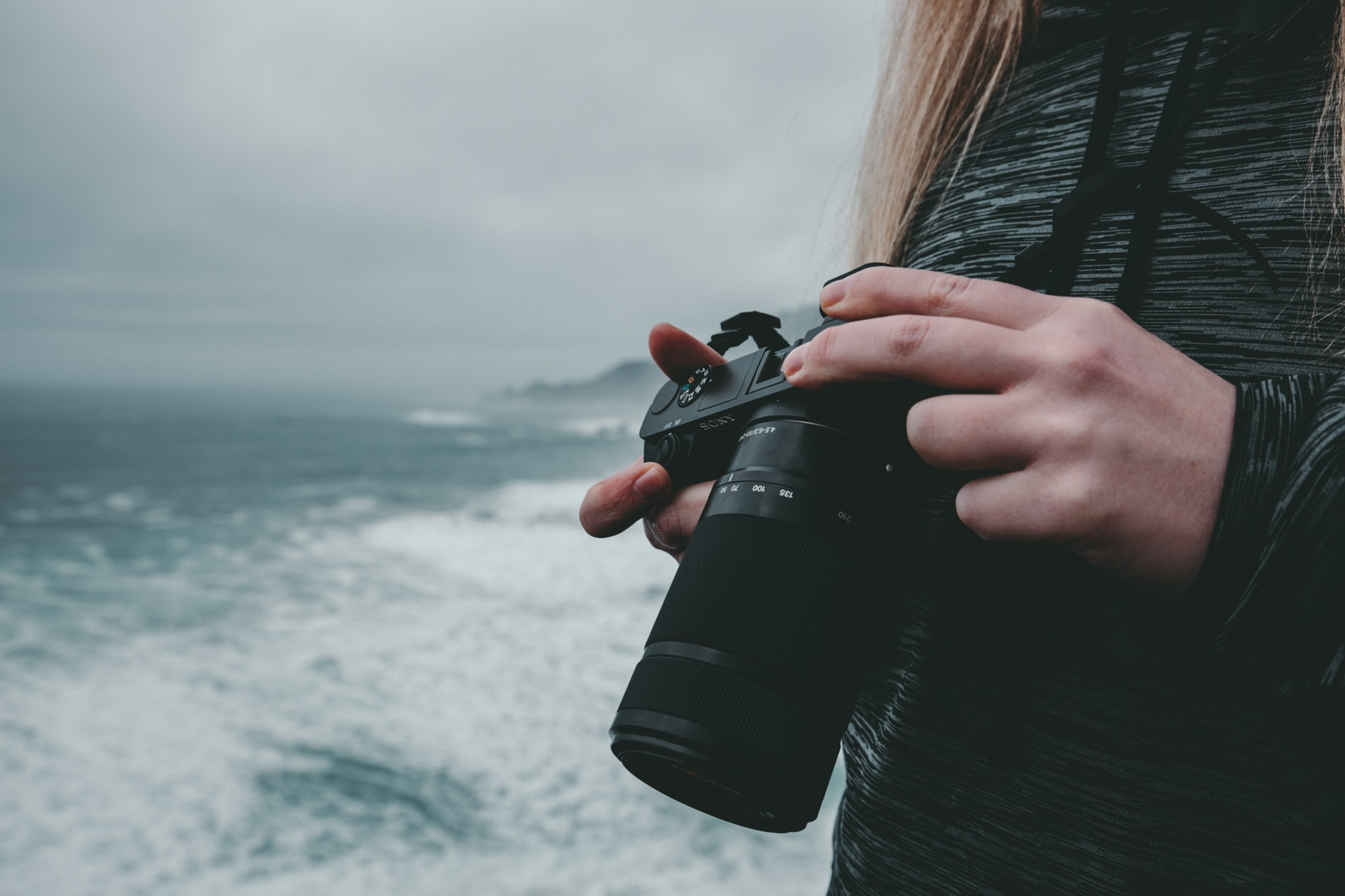 selective focus photography of woman holding camera