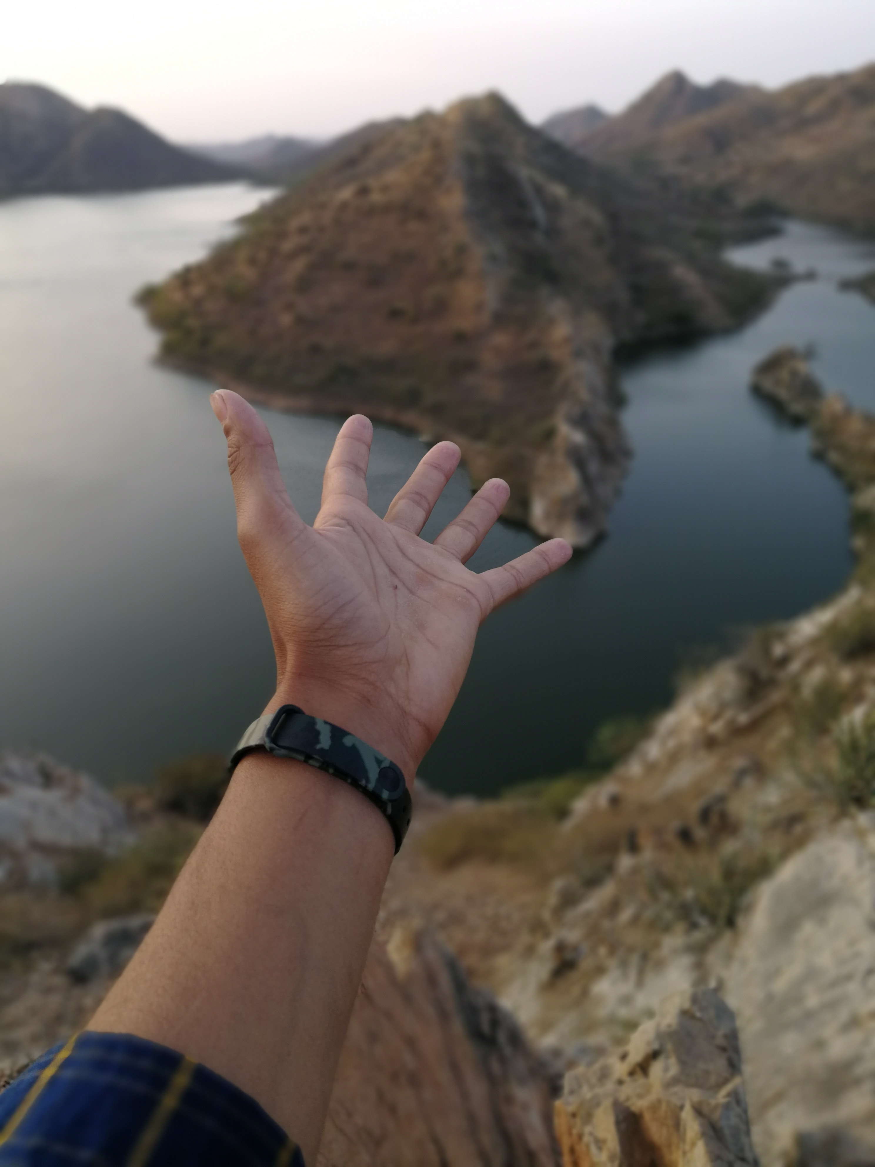 person's hand pointing to body of water and hill