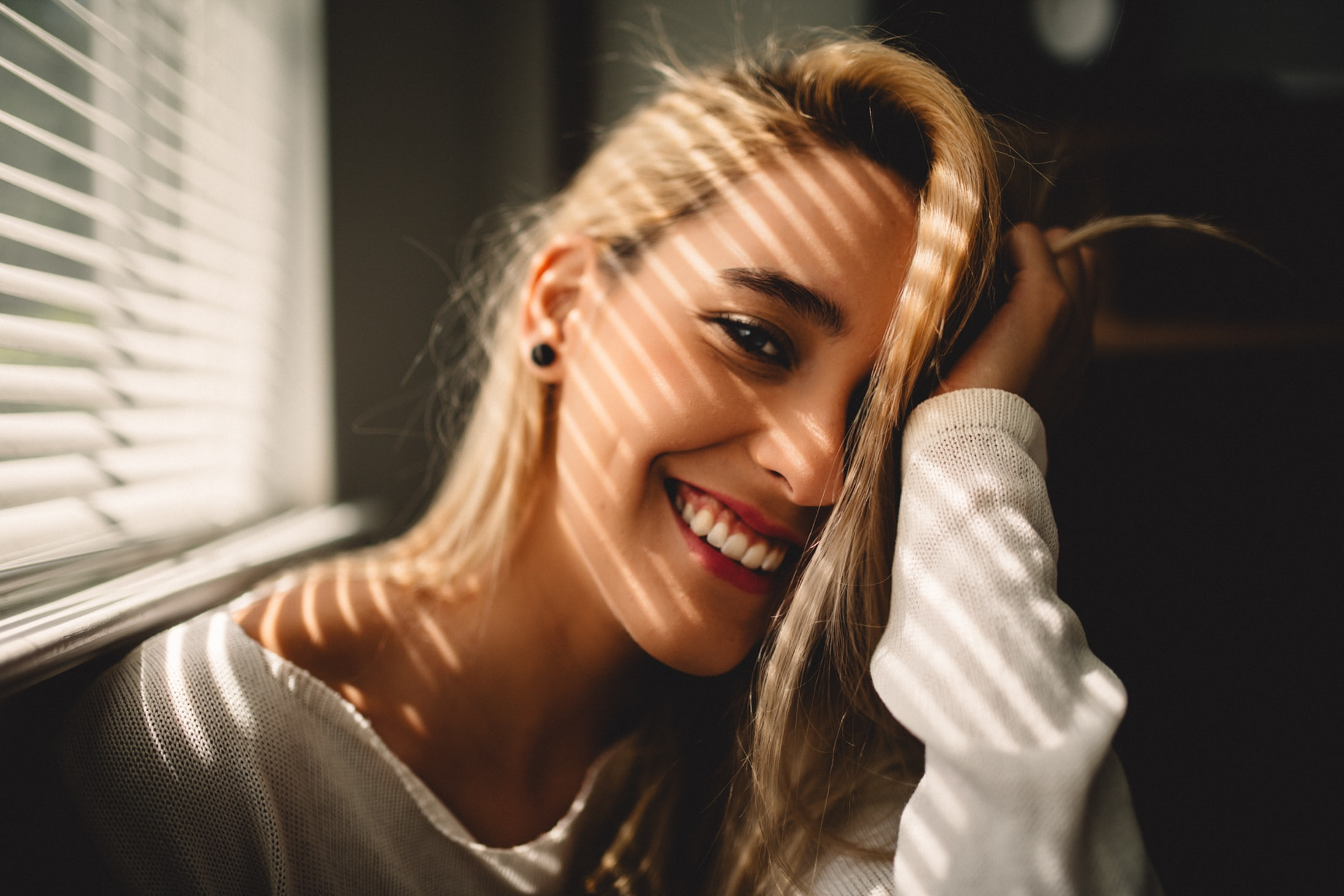 selective focus photography of smiling woman holding her hair beside window blinds