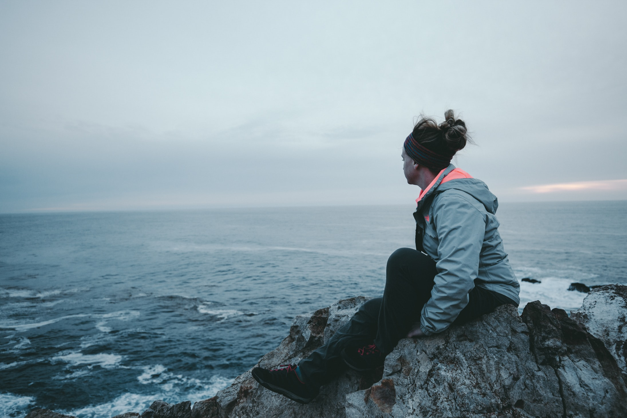 woman sitting on cliff near sea