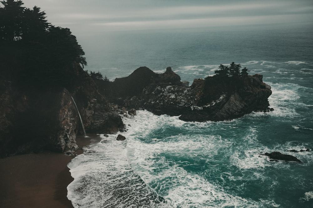 aerial photography of seawaves crashing seashore and rocks at daytime
