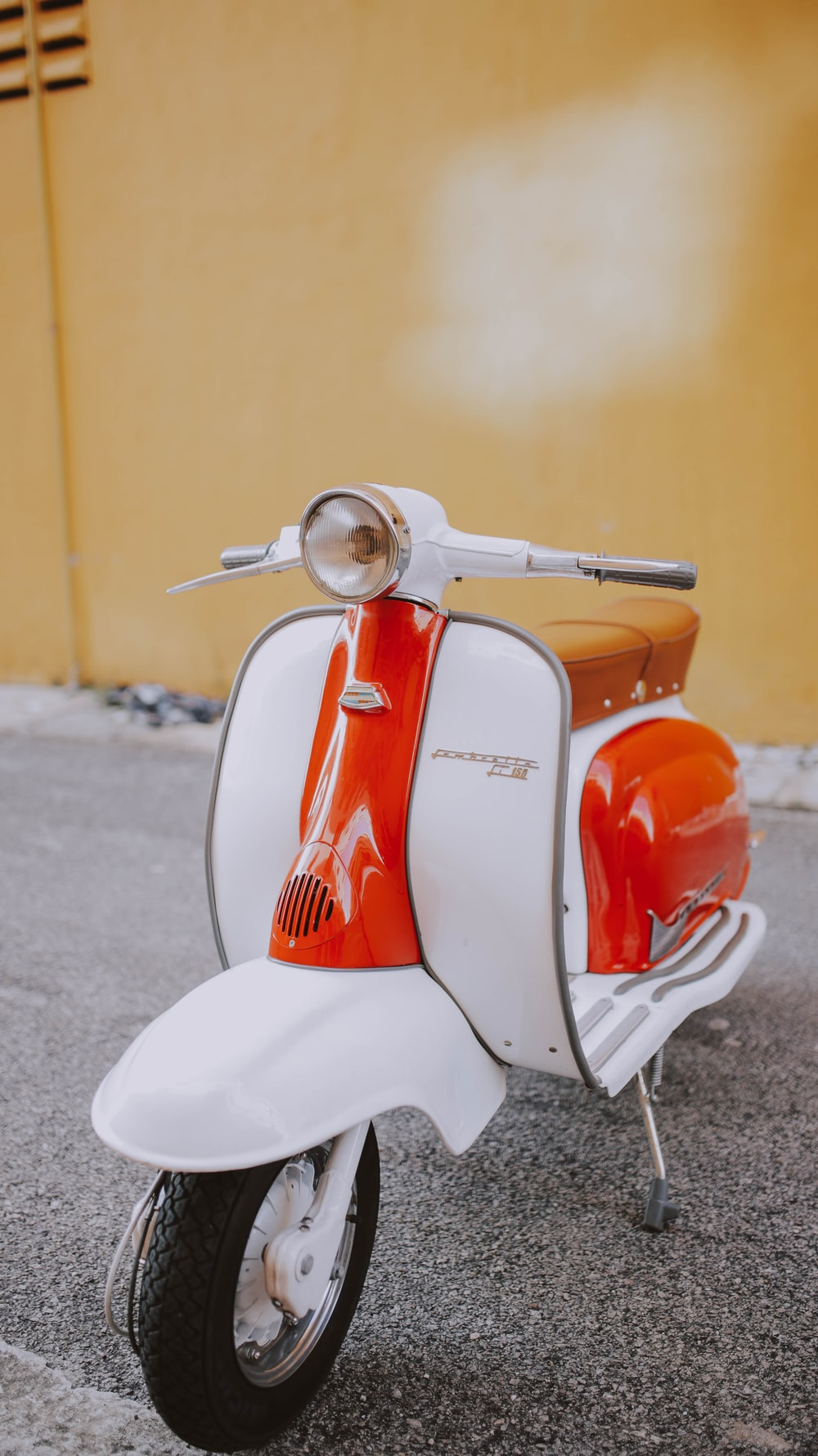 white and orange motor scooter on gray flooring