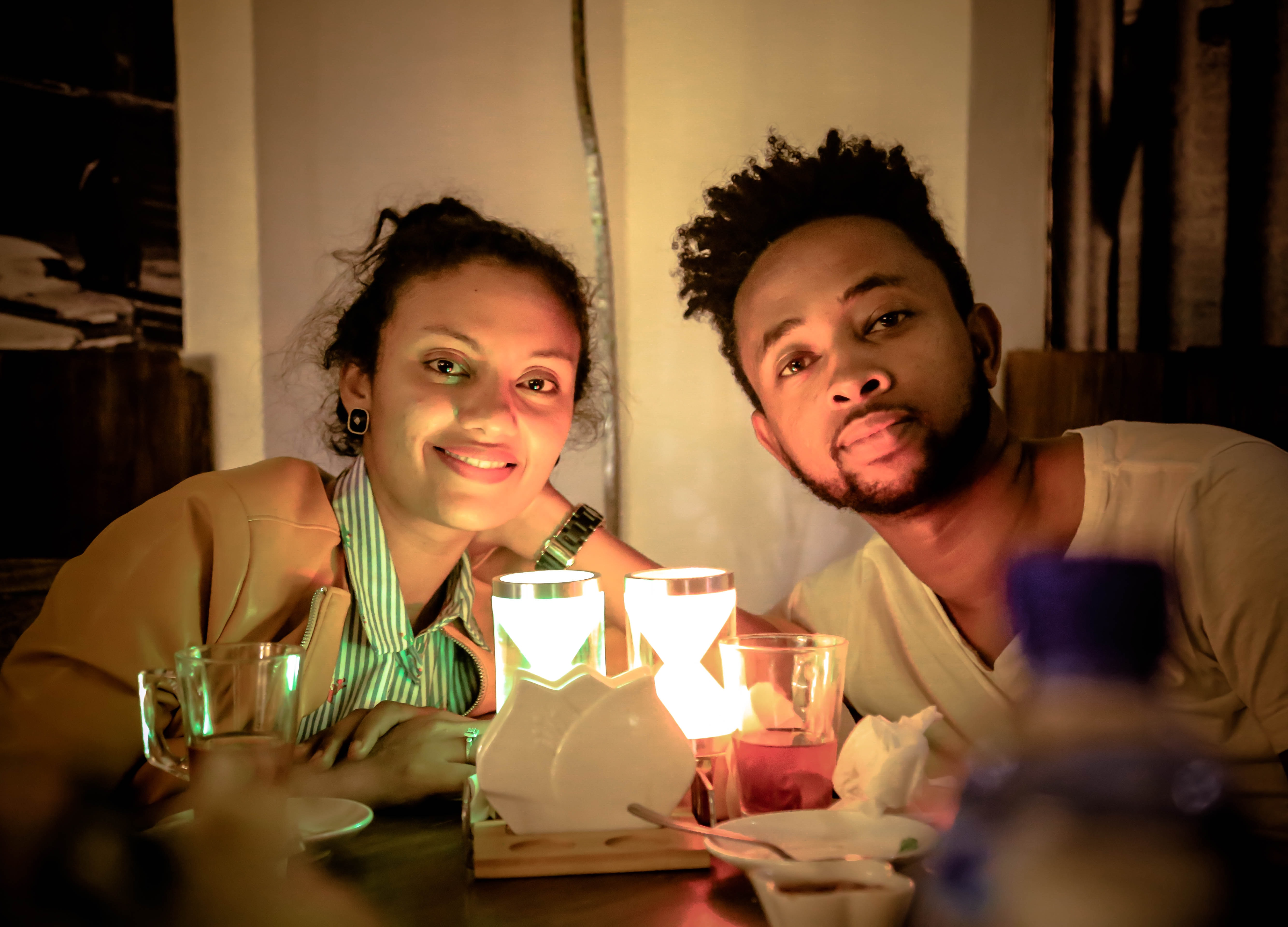 man and woman beside candles