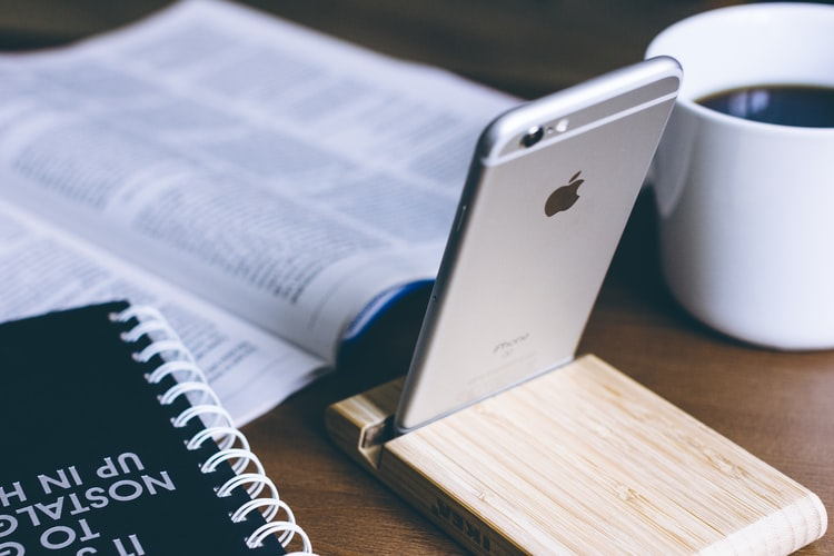 image of phone, books , and mug with coffee on table