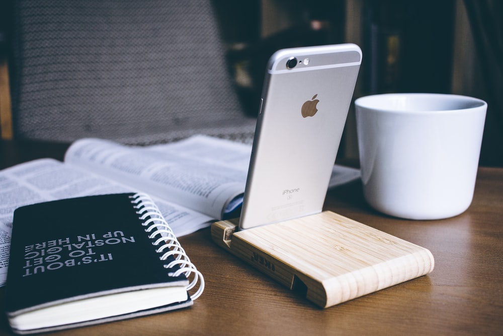 silver iPhone 6 beside white ceramic mug