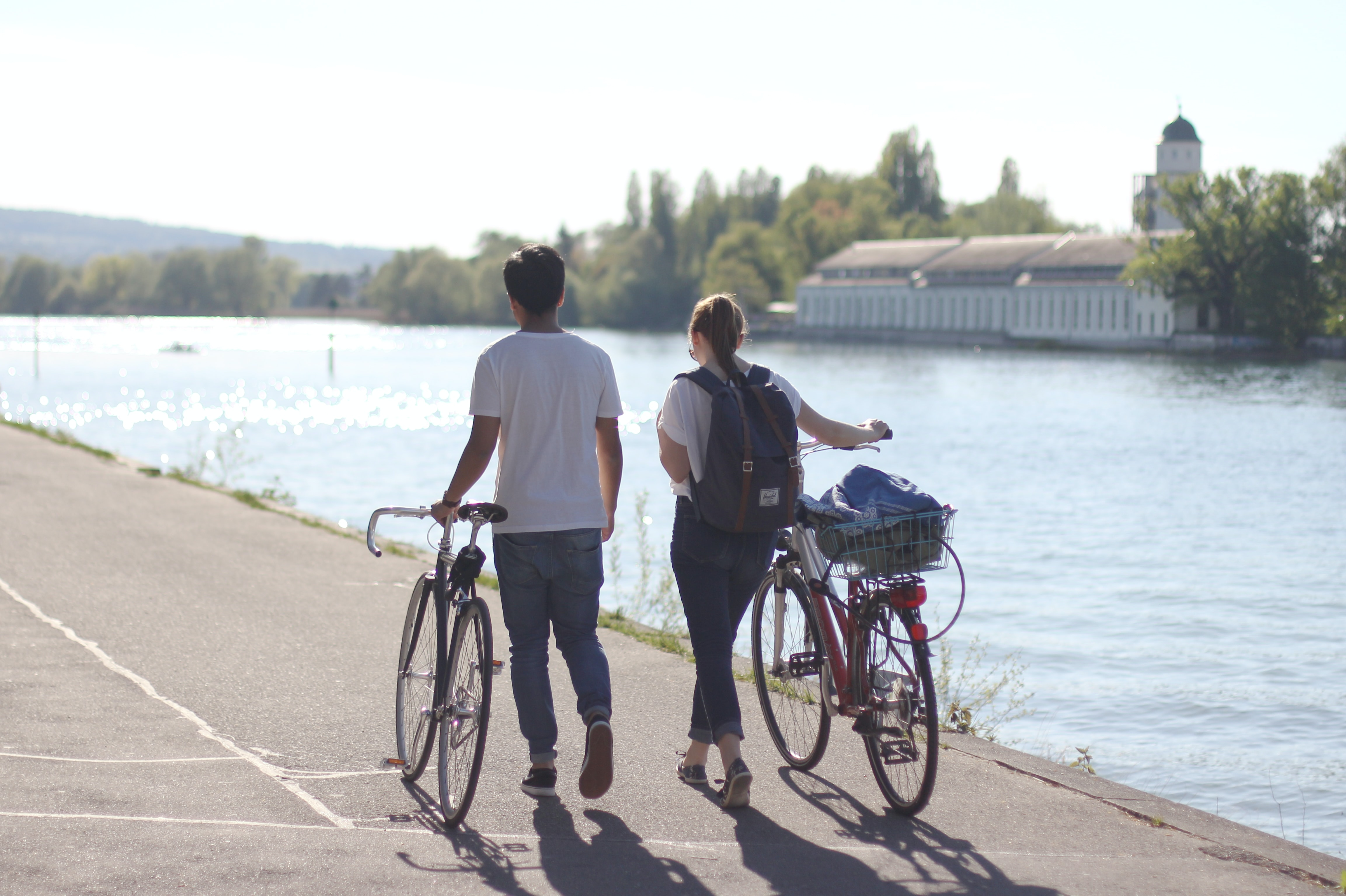 man and women walking holding their bicycles beside body of water